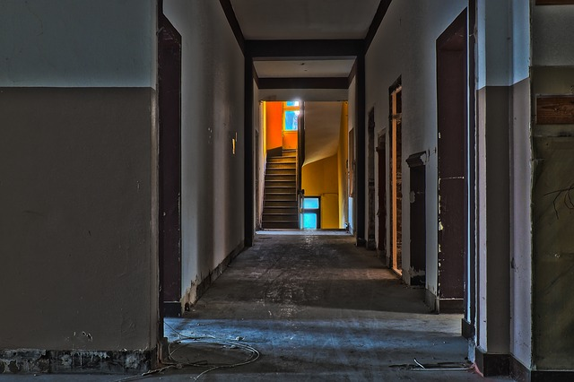 The hallway of an old building with a staircase in the distance