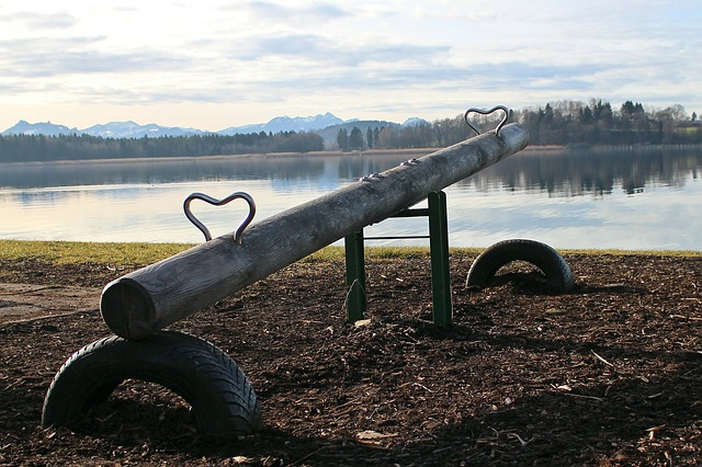 A metal seesaw by a lake with mountains in the background.