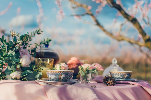 Fancy tea cups and flowers on a pink table cloth against a lovely natural scene