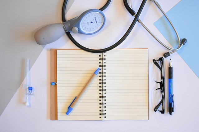 A notepad with glasses and a stethoscope around it