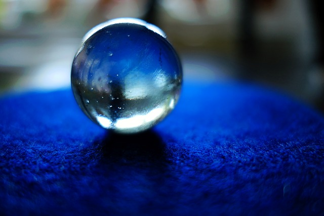 A glass ball sits on a blue tablecloth against a darkened, blurred background