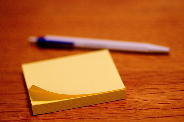 Close up of a stack of yellow post-it notes and a blurred pen in the background.