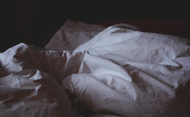 Crumbled blankets in a dark room